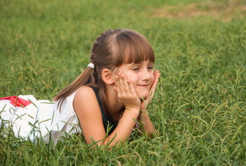 Little cute girl lying on the grass and smiling