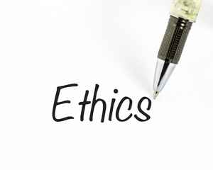 Pen writes ethics word on paper