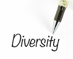 Pen writes diversity word on paper.