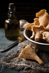Chanterelle mushrooms in a dish on the table and an oil bottle