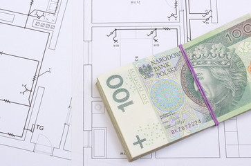 Heap of banknotes on construction drawing of house