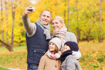 happy family with camera in autumn park