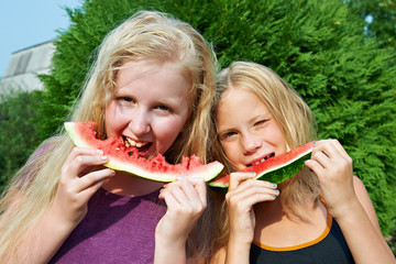 Happy girls eating watermelon