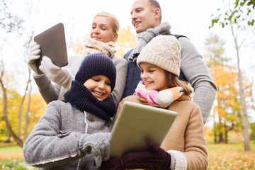 happy family with tablet pc in autumn park