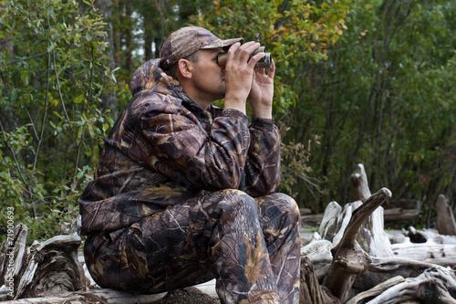 Leinwandbild Motiv sitting hunter looks out the game