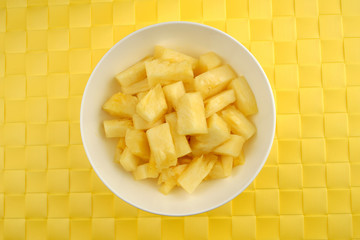 Bowl of juicy pineapples against a textured background