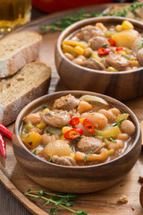 vegetable stew with sausages in a wooden bowl, vertical