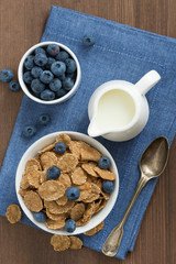 wholegrain flakes with blueberries and milk, top view