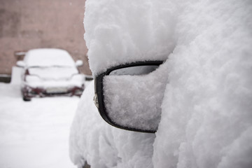 Snow-covered car in the parking lot