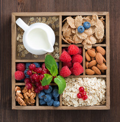 wooden box with breakfast items - oatmeal, granola, nuts, berry