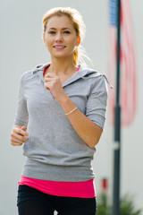 Attraktive junge Frau joggt Outdoor