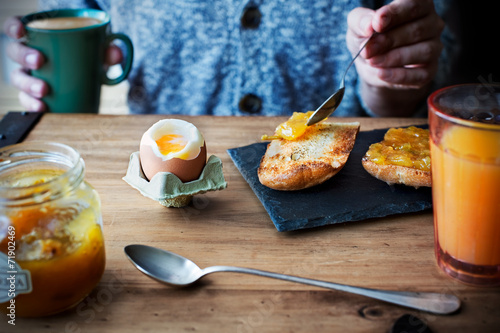Breakfast with soft boiled egg, orange juice and toast with jam - 71902469