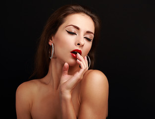 Hot sexy exciting woman with hand near red lips on black