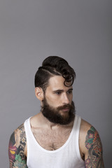 Studio portrait of young man with beard and tattoos