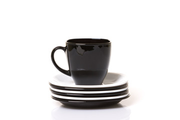 Black cup on the white and black stack of the plates.