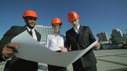 Three confident business architect in protective helmet standing
