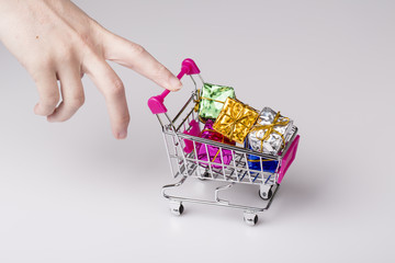 pink shopping cart in woman hand and blue gift