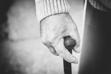 Closeup of old man hand with walking stick