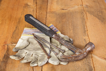Rusty hammer, gloves and nails on wooden table