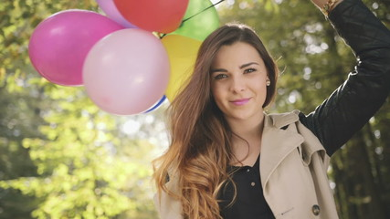 Cheerful brunette with colorful balloons smiling in autumn park.