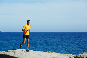 Male jogger in fluorescent t-shirt runs over sea rocks