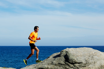 Young athlete running fast jumping over rocks at sunny day