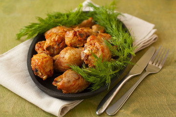 baked chicken drumsticks and fresh dill on a wooden background