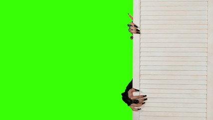 Vampire woman peeking out from behind the door on green screen.