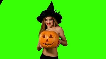 Halloween witch holding a orange pumpkin on green screen.