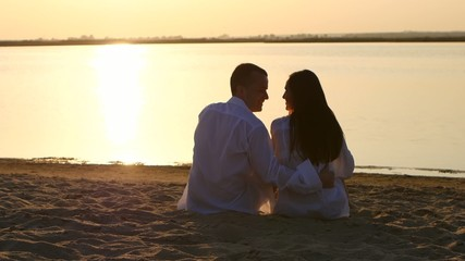 Young couple kissing on the bank of a river at sunset