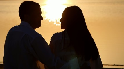 Silhouette young couple kissing on the bank of a river at sunset