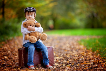 Little boy with suitcase and teddy bear