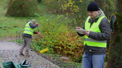 Foreman working with tablet PC near worker who collect leaves