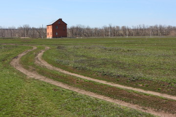 Earth road leading to a lonely red brick cottage in the meadow