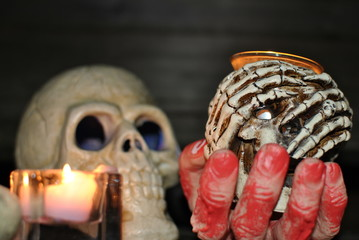 hand covered in blood holding skull