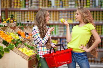 Две девушки в продуктовом магазине с фруктами