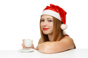 Beautiful young woman in santa claus hat sitting at the table wi