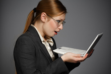 Surprised business woman with white netbook