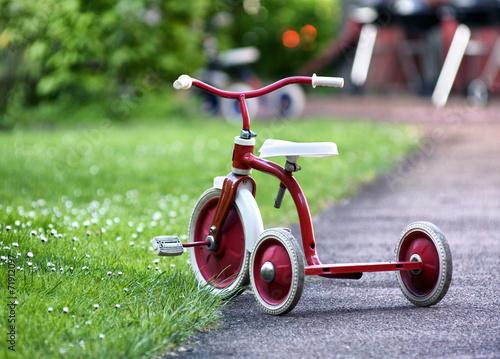 Leinwanddruck Bild red child tricycle in a garden