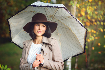 Beautiful woman with umbrella in autumn park