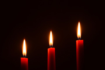 Three red candles on a black background