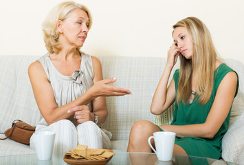 Young woman and mature mother having serious talking
