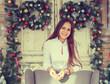 Smiling teenage girl having fun over christmas decoration backgr