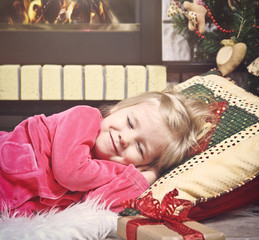 Little cute girl sleeping under the Christmas Tree waiting for S