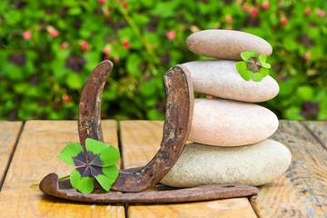 Steinturm, Hufeisen und Kleeblätter auf Holz, Textfreiraum