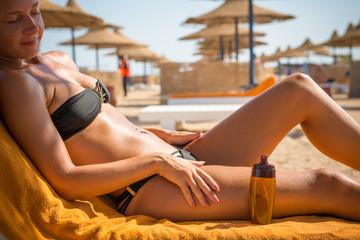 Sensuous slim woman applying suntan oil