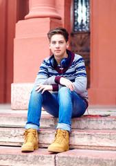 stylish teenage boy with headphones, sitting on stairs