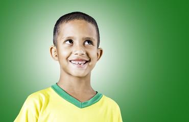 Little Brazilian boy smiling on green background