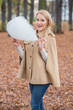 Cute stylish woman eating candy floss