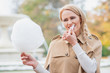 Pretty blond woman eating candy floss